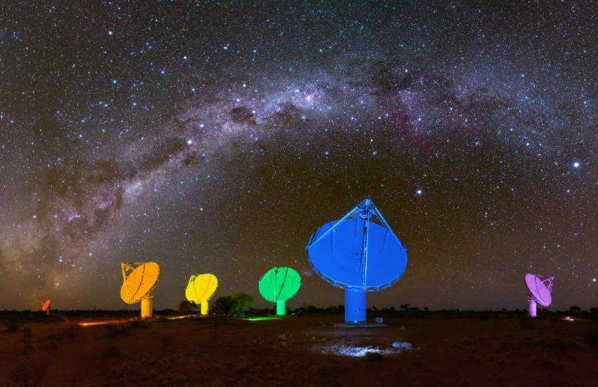 Six dish antennas lit up in rainbow colors against a starry night sky.