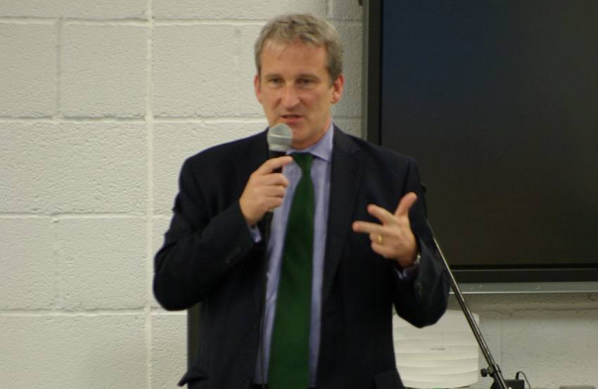 Damian hinds standing in a suit talking into a microphone