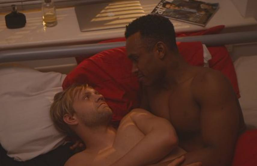 two men lying side by side in bed, they are looking at each other