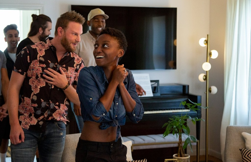 a woman looks around a living room smiling, with the queer eye guys standing behind her