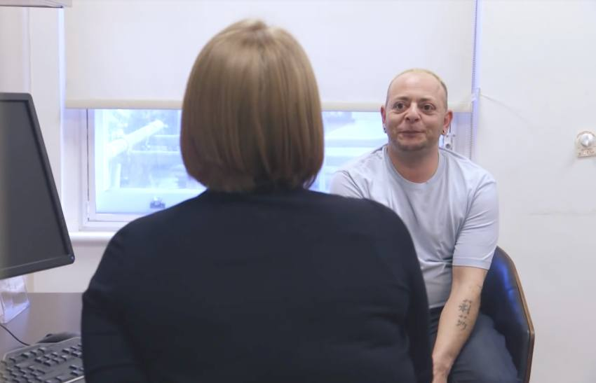 a patient sitting in the doctors office. he is wearing a white t-shirt and facing the doctor whose back is to the camera