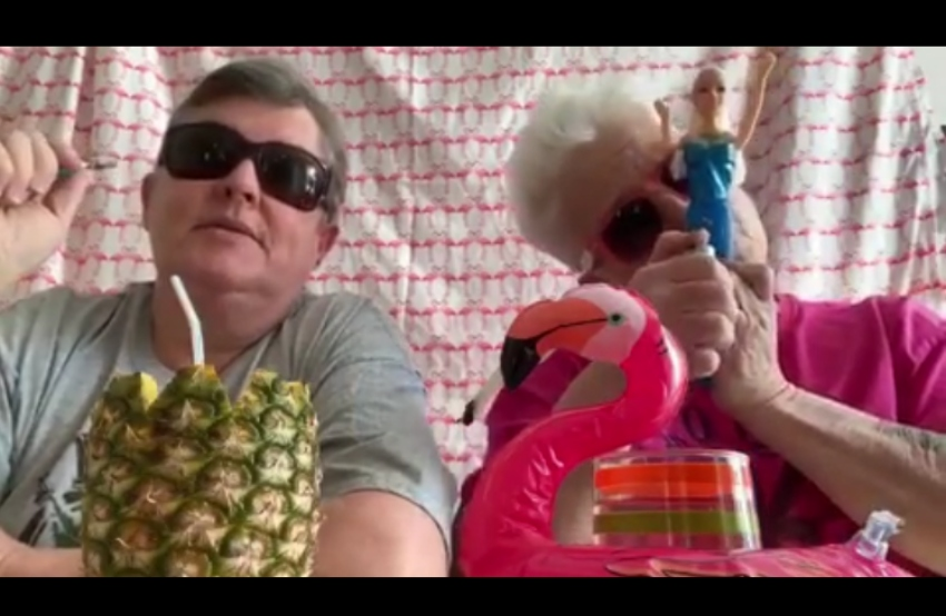 two women in sunglasses with a pineapple and inflatable flamingo. one is smoking a bong made from a barbie doll