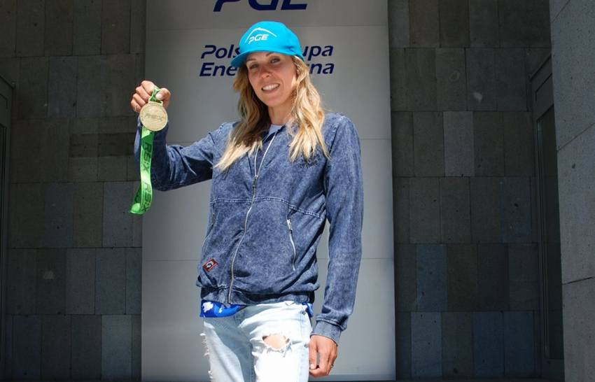 Sofia klepacka standing on steps outside a building holding up a medal