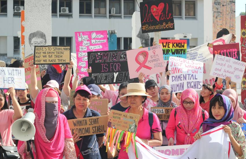 women dressed in pink holding placards at women's day march