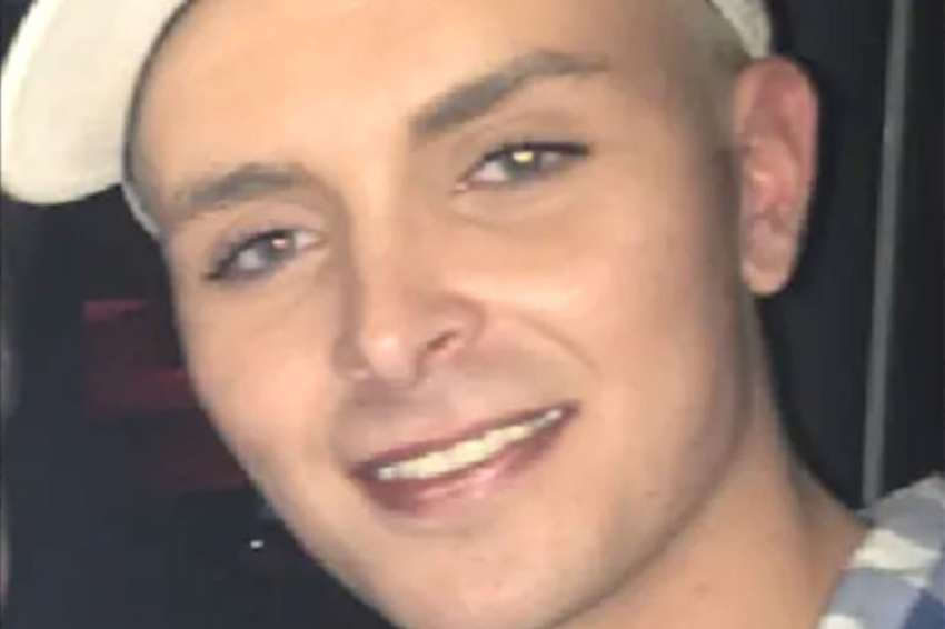 a close up photo of a young man who is smiling and wearing a white cap