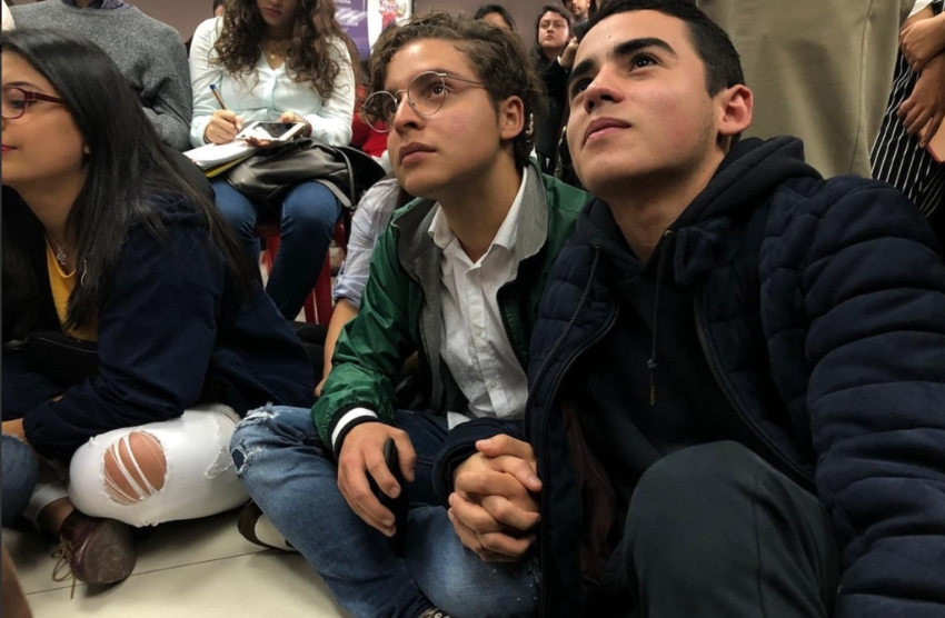 two young people sit cross-legged on the ground looking up at something above them