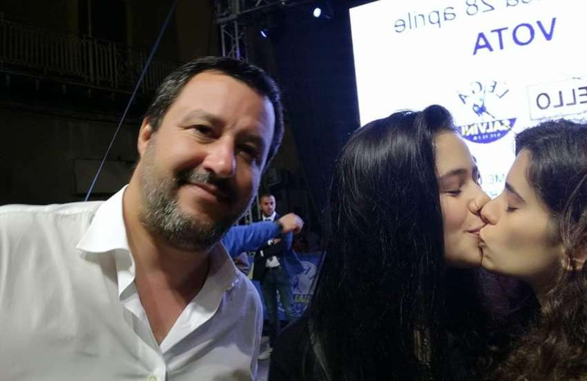 a selfie with a man in the white shirt looking at the camera, with two women kissing on the lips next to him