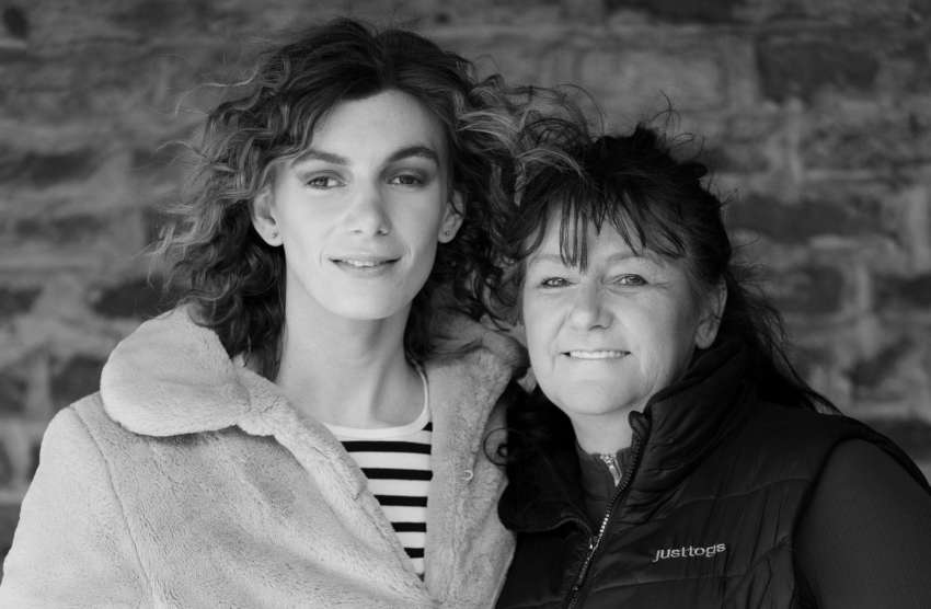 a black and white photo of two women standing closely next to each other