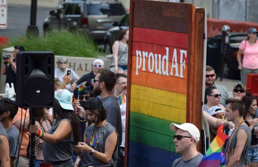 a rainbow sign reading 'proud af' at a pride parade surrounded by people