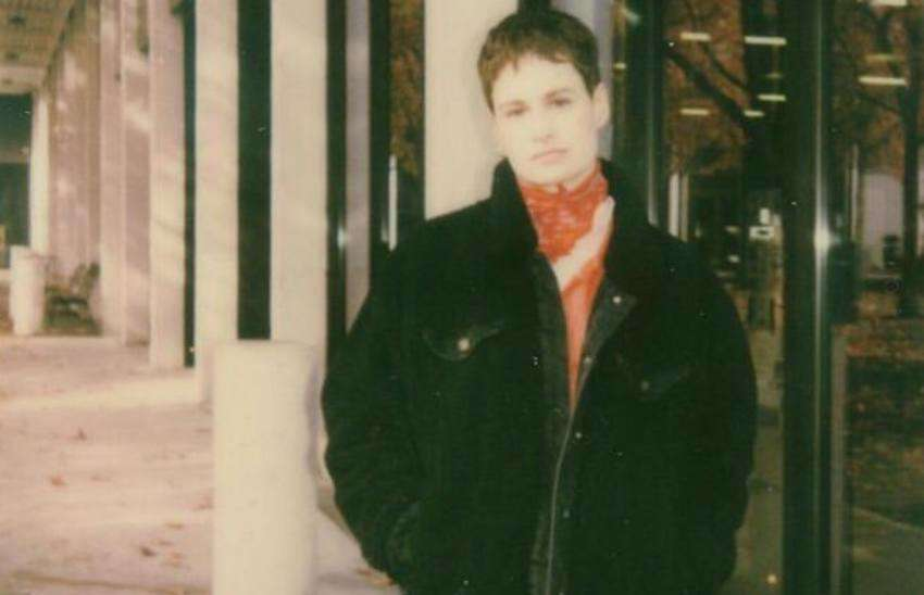 a grainy vintage shot of Christine and the queens who is standing with her hands in her jacket pocket in front of a building