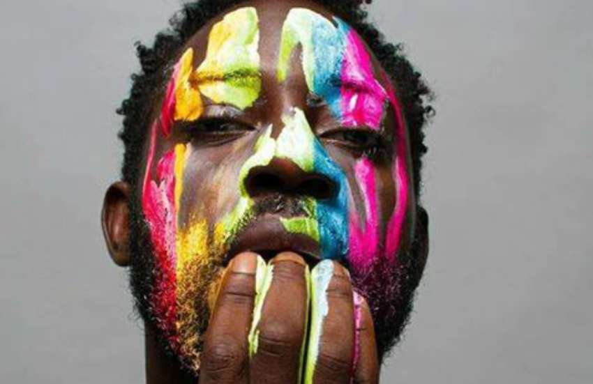 a man with short dark hair, with rainbow paint down his face