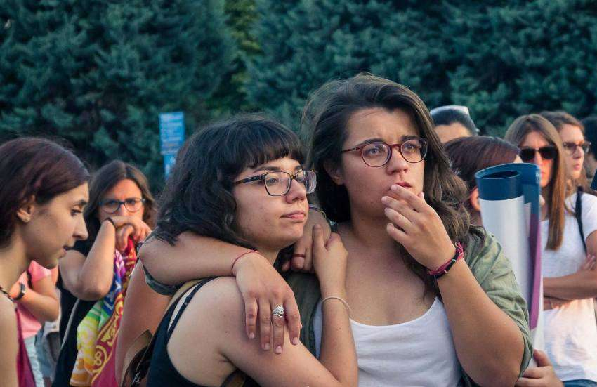 two women stand together with their arms around each other in a crowd of people