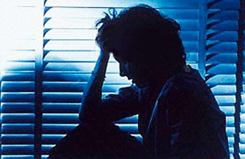 a person sitting in front of window blinds with their hand on their forehead
