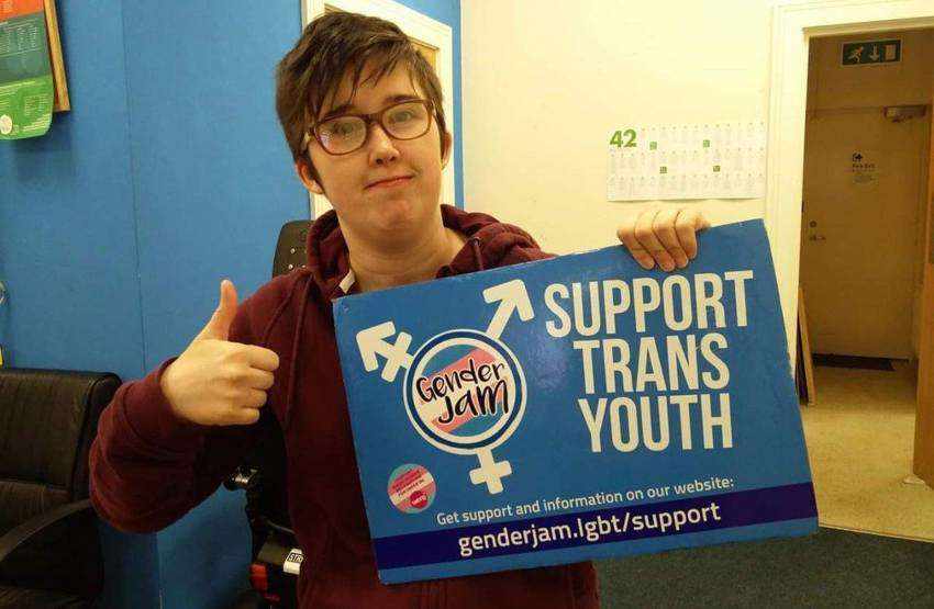 a person holds a sign reading 'support trans youth' and giving the thumbs up
