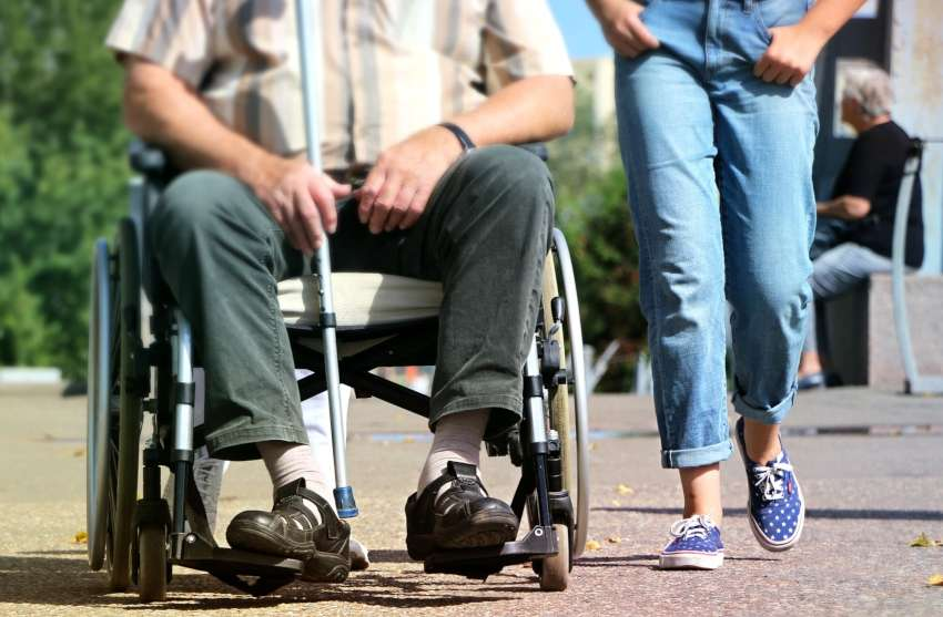 a man in a wheelchair with a person walking beside them in jeans. the shot only shows their legs