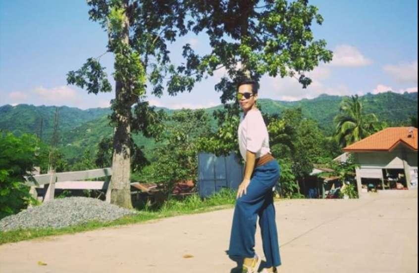 a person striking a pose while standing outside in front of a tree