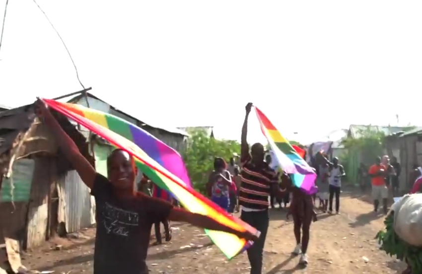 people running through a dusty street with rainbow flags held above their heads