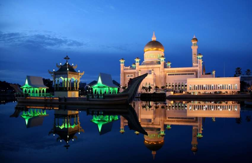 A royal palace in brunei at night, the building is reflected in the body of water in front of it