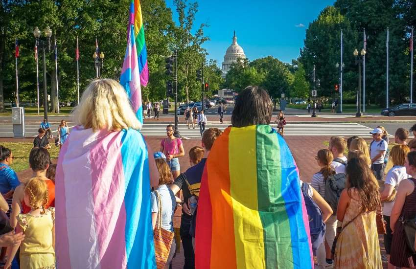 People draped in a pride and transgender pride flag look on to Congress