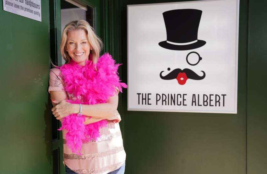 a blonde woman wearing a pink boa stands outside a bar where the sign reads the prince albert