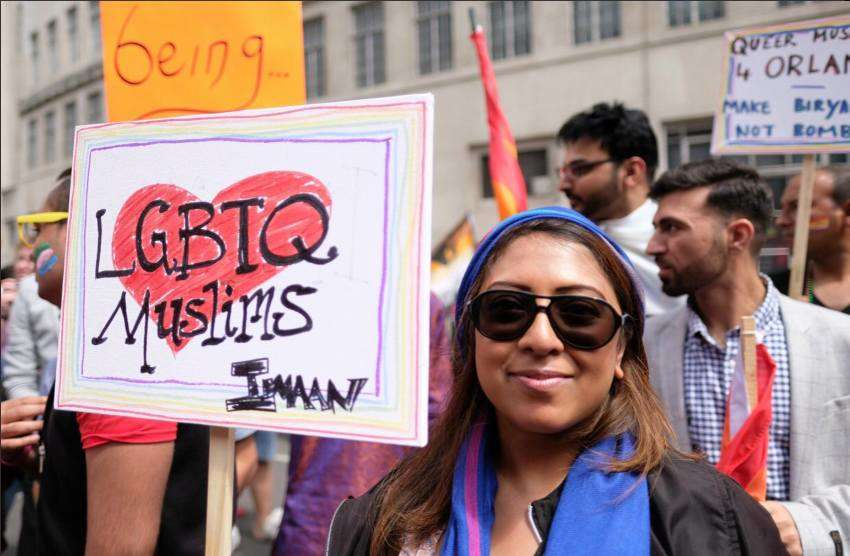 a woman holding a sign with a love heart at a pride parade