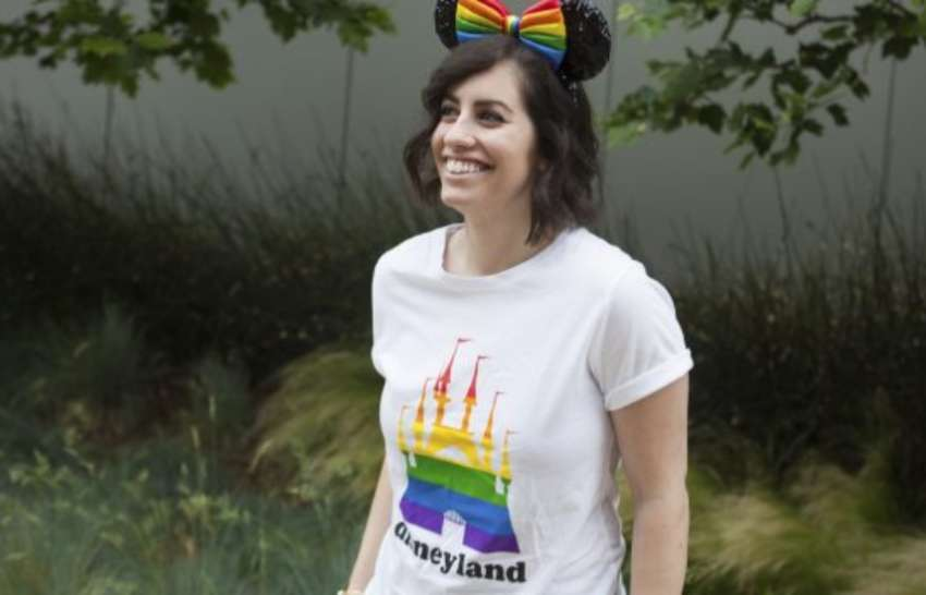 A woman in a white t-shirt that has a rainbow castle on it, she has a rainbow headband on