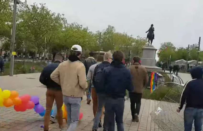 a group of young men vandalizing rainbow flags and balloons