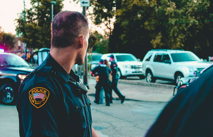 A police officer in the foreground, looking at his colleagues performing an arrest in the background.