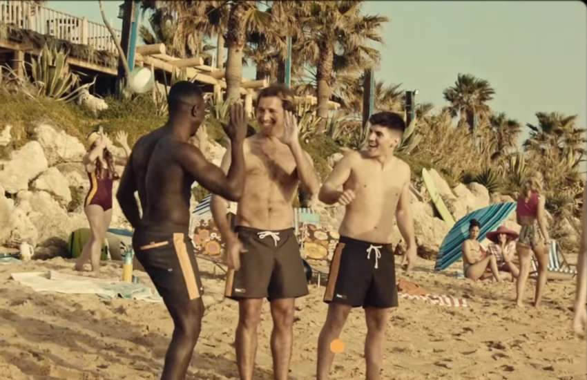 three men on a beach high-fiving each other