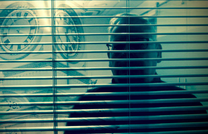 An older man looks through blinds