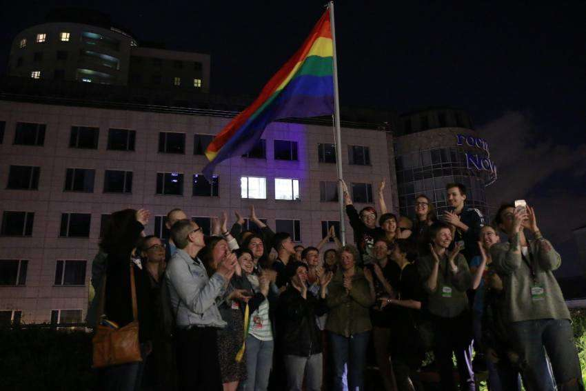 people raising a rainbow flag at night in a square in Russia