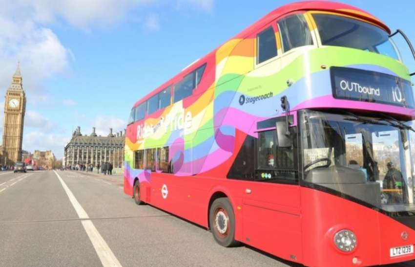 a bus with a rainbow flag wrapping drives over westminster bridge