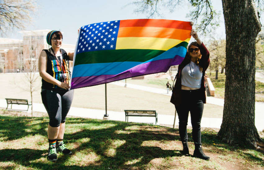 Two students at University of North Texas hold a rainbow flag, March 2018