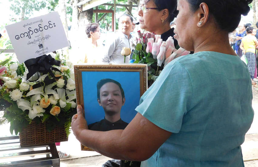 An attendee of the funeral of Myanmar librarian Kyaw Zin Win holds his photograph (Photo: Facebook)