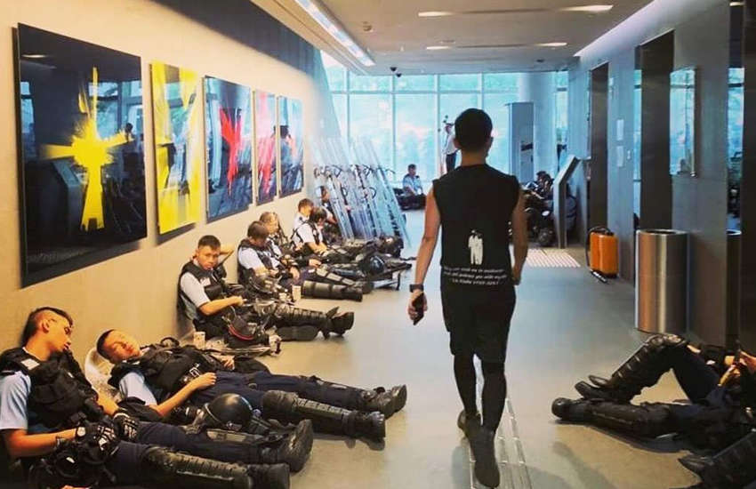 Hong Kong's openly gay lawmaker Ray Chan scolded riot police for resting in parliament's corridors as protestors surrounded the building