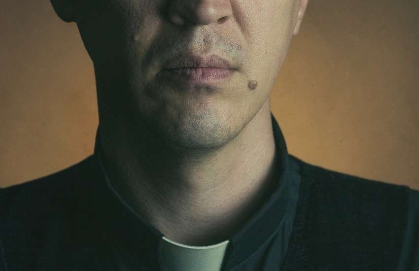 A man wearing the traditional white collar of a priest, a type of religious leader