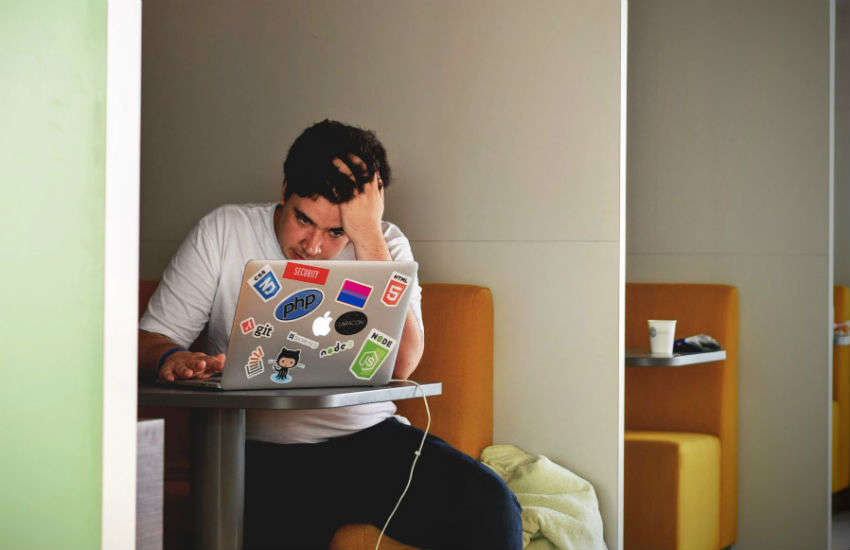 A stressed man stares at his laptop in his workplace