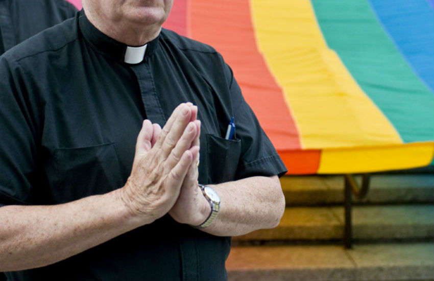 priest standing in front of rainbow flag