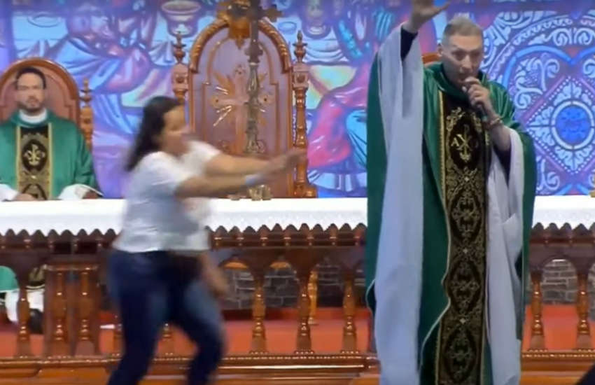 Father Rossi getting pushed off the stage during his sermon