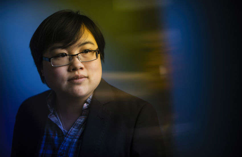 Headshot of Lydia Brown, young East Asian person, with stylized blue and yellow dramatic background. They are looking in the distance and wearing a plaid shirt and black jacket. Photo by Adam Glanzman