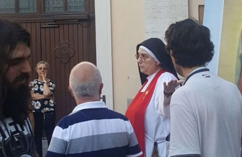 A nun asking anti-gay protesters to leave the church's courtyard during Brianza Pride