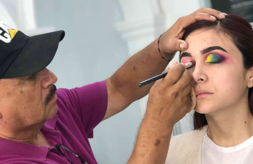 Don Raúl Santiago practices makeup skills in Deysbel Olachea's class