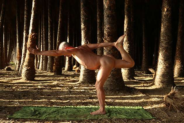 Man does naked yoga in woodland.