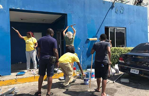 LGBT+ campaigners painting Freeport Police Station in Jamaica.