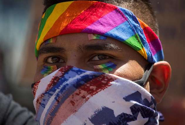 Black Lives Matter protestor with rainbow bandana and stars and stripes face mask.