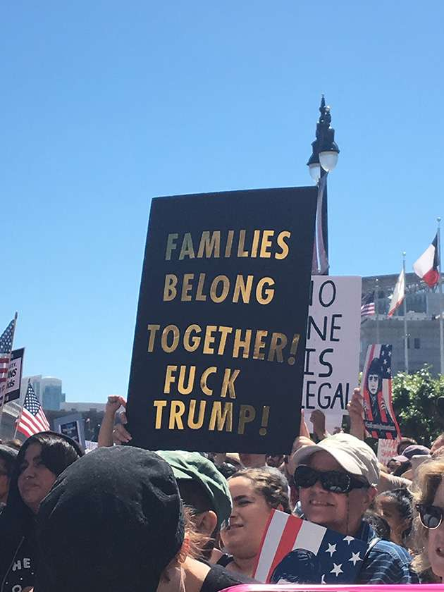 Banner at protest against Trump's immigration policy reads: 'Families belong together! Fuck Trump!'