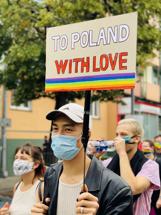 Protestor carries banner saying 'To Poland with Love'.