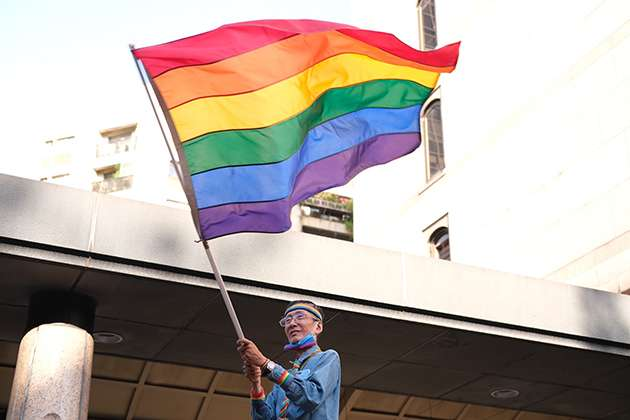 A man waves a rainbow flag.