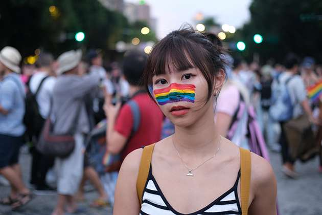 A woman in rainbow face paint.