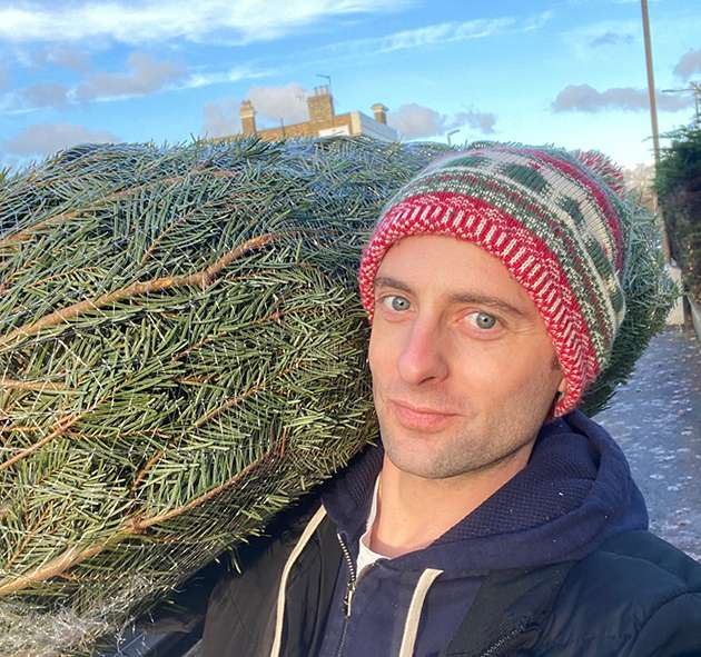 Daniel Harding carrying a Christmas tree.